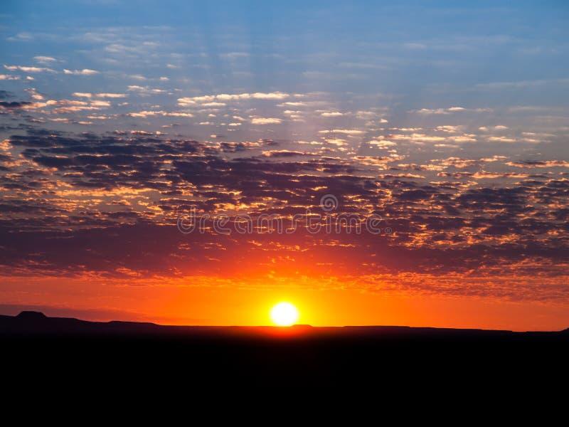 Dorato cielo e nuvole saturati bello tramonto Paesaggio sereno pacifico con la siluetta nera della terra fotografie stock libere da diritti
