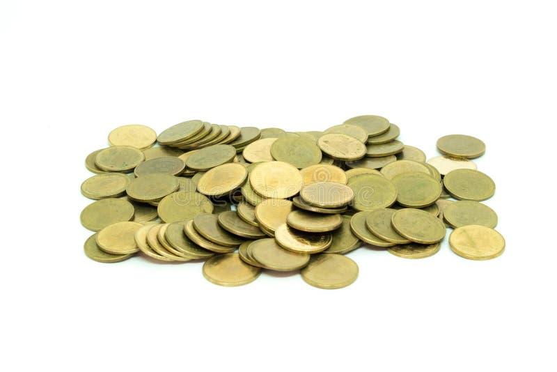 Dorato delle monete isolato su fondo bianco e sul fuoco selettivo fotografia stock