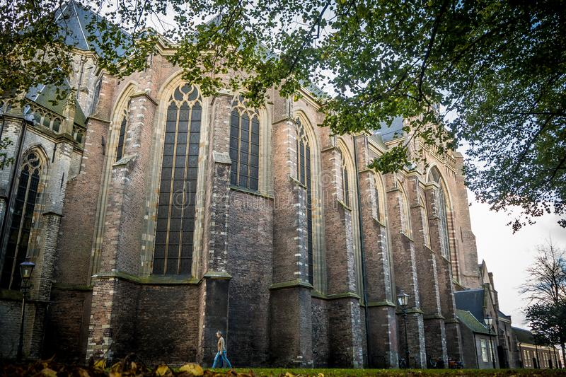 Woman walking by the old gothic Grote Kerk in Dordrecht on an autumn day. Dordrecht, Netherlands - October 27, 2018: A woman walks by the old gothic Grote Kerk royalty free stock photos