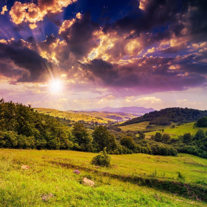 Dorf auf Abhangwiese mit Wald im Berg bei Sonnenuntergang lizenzfreies stockbild