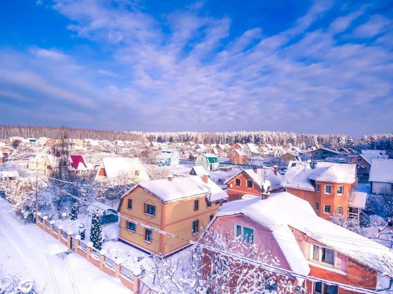 Dorf in der Waldwintervogelperspektive Geben zum Blau stockfoto