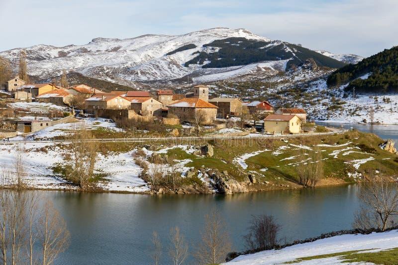 Dorf des Gebirgsschnees auf der Steigung eines Reservoirs im Winter stockbild