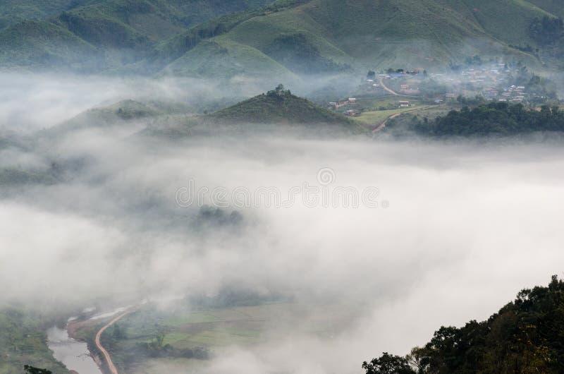 Dorf im Nebel im Winter lizenzfreie stockfotos