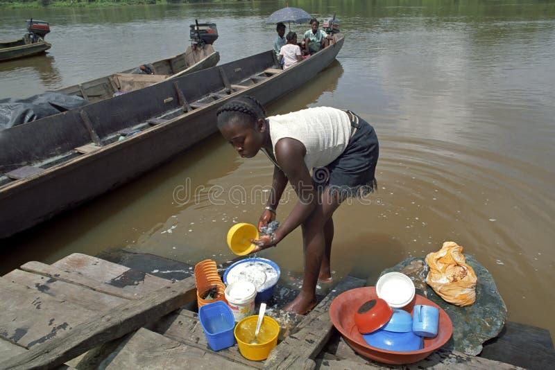Dorf-Leben, waschende Teller im Fluss stockfotos
