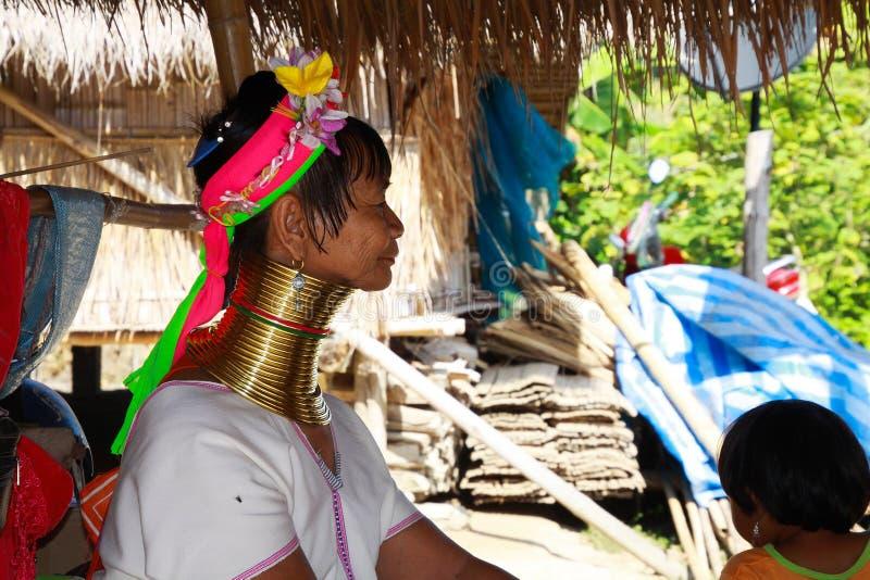 DORF LONGNECK KAREN, THAILAND - 17. DEZEMBER 2017: Gealterte alte lange Halsfrau, die vor einer Bambushütte mit Strohdach sitzt lizenzfreie stockfotos