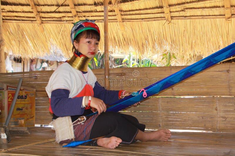 DORF LONGNECK KAREN, THAILAND - 17. DEZEMBER 2017: Lange Halsfrau, die Handarbeit unter Strohdach tut lizenzfreies stockbild