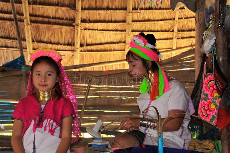 DORF LONGNECK KAREN, THAILAND - 17. DEZEMBER 2017: Zwei Mädchen vom langen Halsstamm, der in der Hütte spielt lizenzfreie stockfotografie