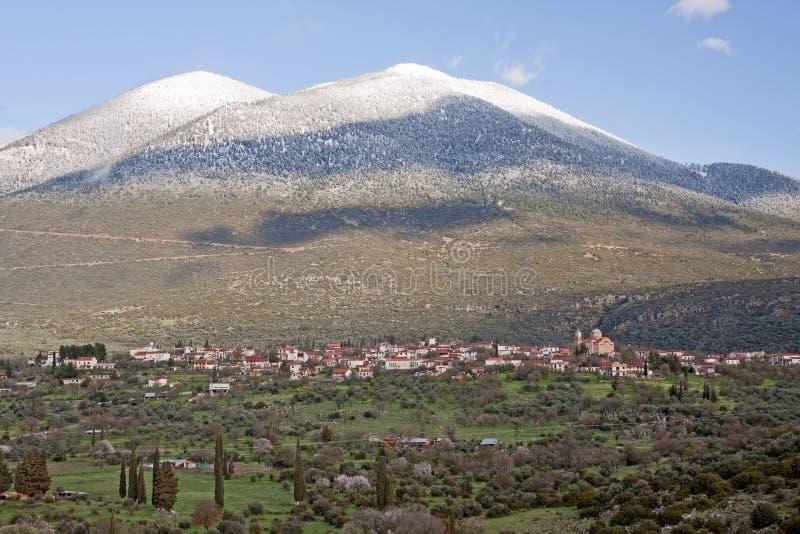Dorf und Schnee-mit einer Kappe bedeckter Berg lizenzfreie stockbilder