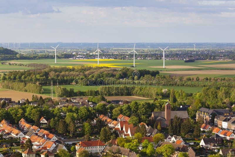 Dorf und Windkraftanlagen in der flachen Landschaft stockbild