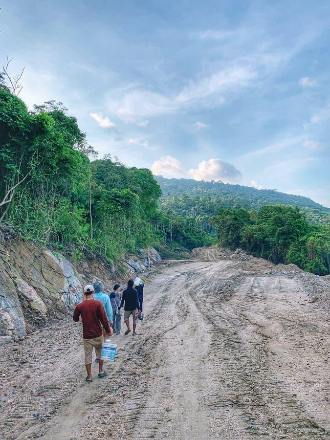 Dorfbewohner gehen auf den Schotterweg zu ihrem Dorf im südlichen von Thailand lizenzfreie stockfotografie