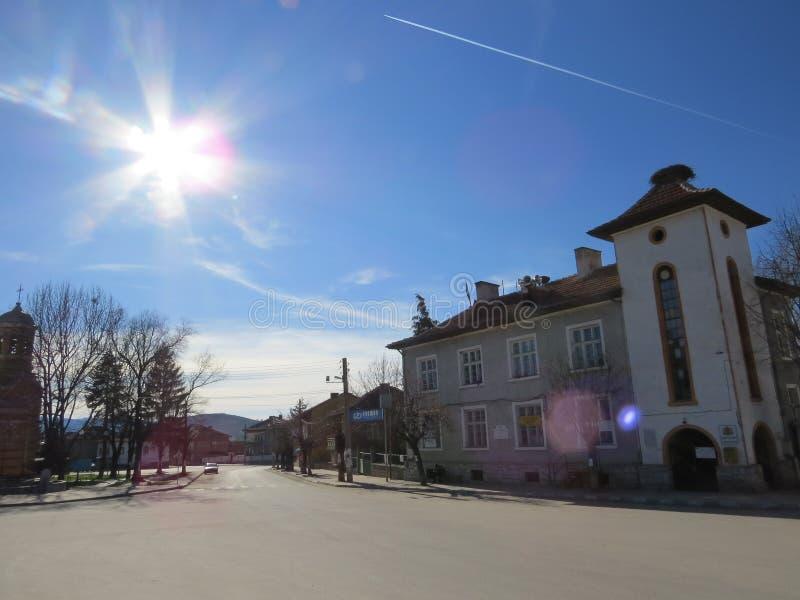 Dorfhauptplatz an einem hellen blauen sonnigen Tag Flugzeug im Himmel lizenzfreies stockbild
