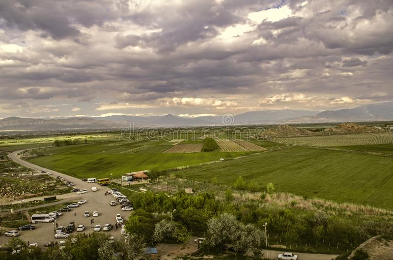 Darkened spring sky over the road leading to the medieval monastery of Khor Virap among gardens and vineyards on the background of. Ararat valley with darkened stock photos