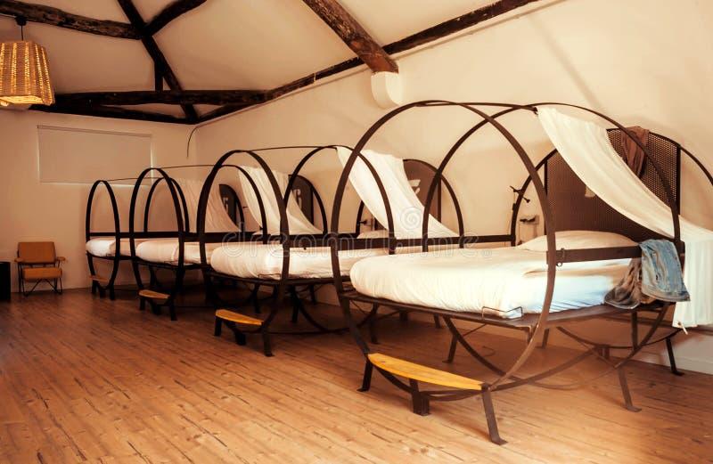 Dorm pokój wśrodku schronisko sypialni z czystymi białymi łóżkami dla uczni i turystów zdjęcie stock