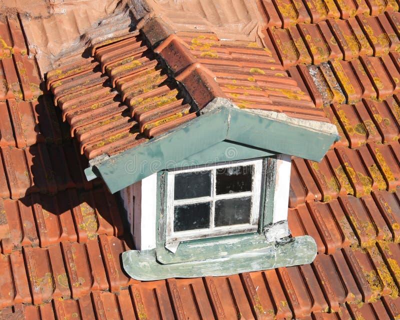 Dormer em um telhado vermelho velho da telha fotografia de stock
