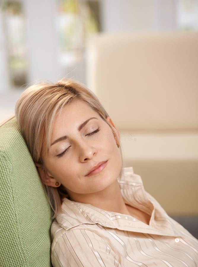 Dormida da mulher na poltrona em casa imagens de stock
