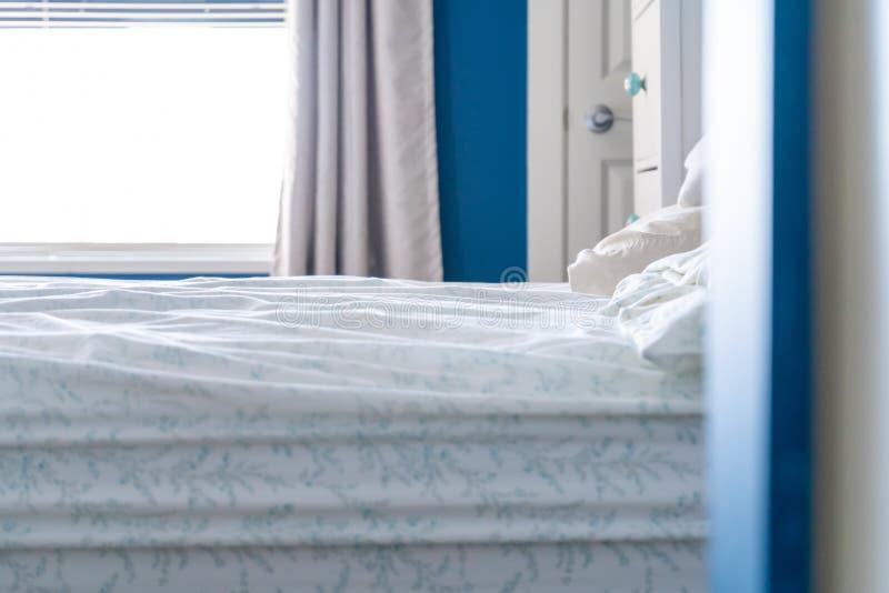 Dormir-en cama con una hoja sucia, ningunas mantas, en un diseño azul y blanco del hogar del dormitorio imagen de archivo