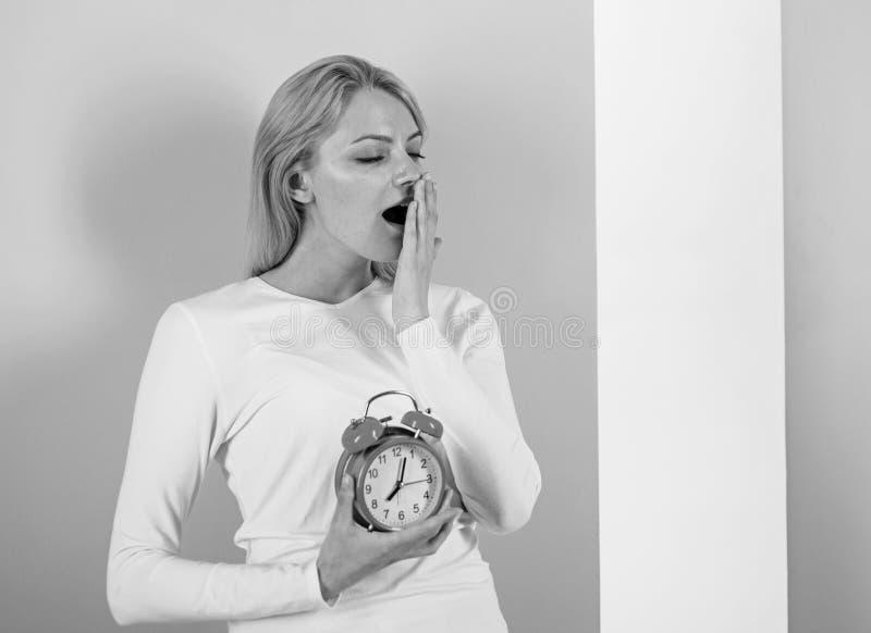Dormir trop longtemps des effets secondaires est trop de sommeil néfaste Le visage de baîllement de fille a juste réveillé le fon photographie stock