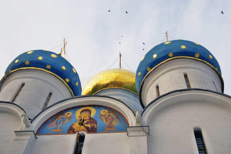 Dormition church of Trinity Sergius Lavra. Birds fly around cupolas stock images