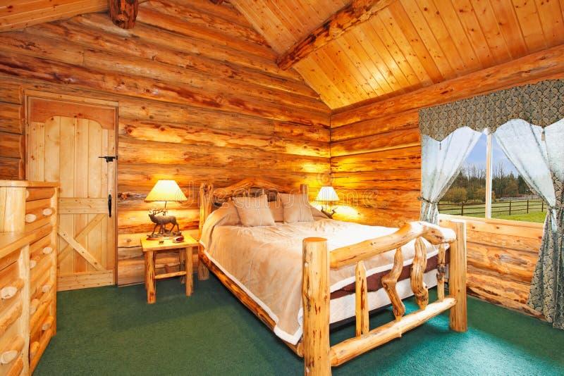 Dormitorio acogedor en casa de la cabaña de madera foto de archivo
