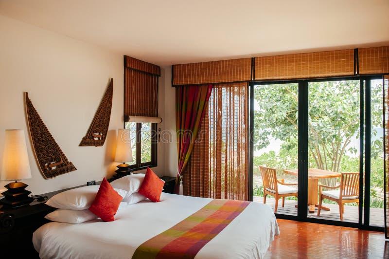 Dormitorio acogedor tropical tailand?s del hotel - decoraci?n asi?tica del hogar del vintage imagen de archivo libre de regalías