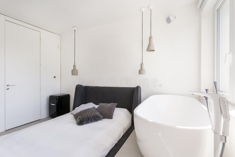 Dormitorio ascético con la bañera oval fotos de archivo libres de regalías