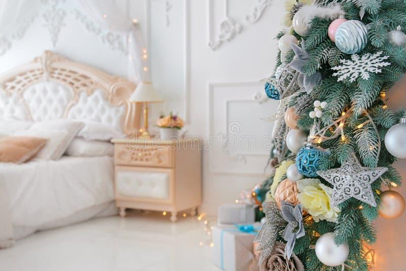 Dormitorio blanco brillante interior con la decoración del árbol del Año Nuevo de la Navidad y el bokeh de las luces en el fondo imágenes de archivo libres de regalías