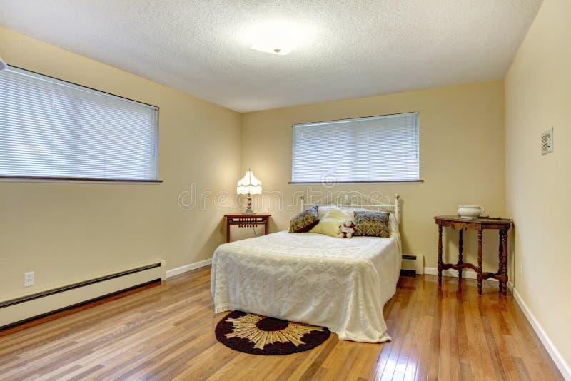 Dormitorio brillante con el marco de la cama del hierro foto de archivo