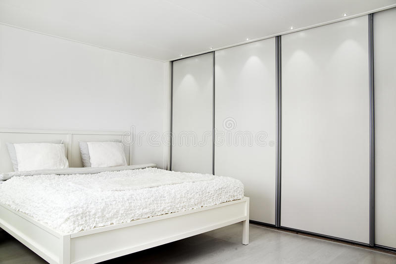 Dormitorio. Cama y un armario. fotografía de archivo libre de regalías