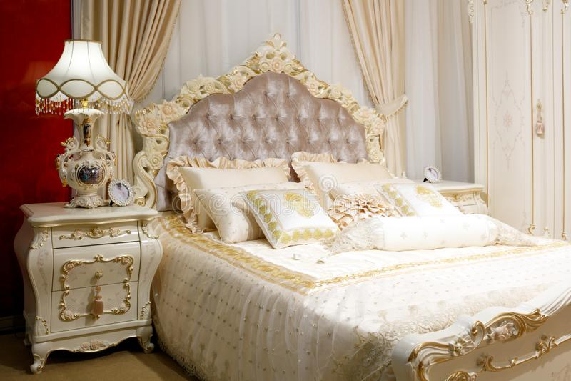 Dormitorio clásico moderno de lujo del estilo en los tonos blancos y rosados, interior del dormitorio, muebles con un ornamento d imagen de archivo libre de regalías