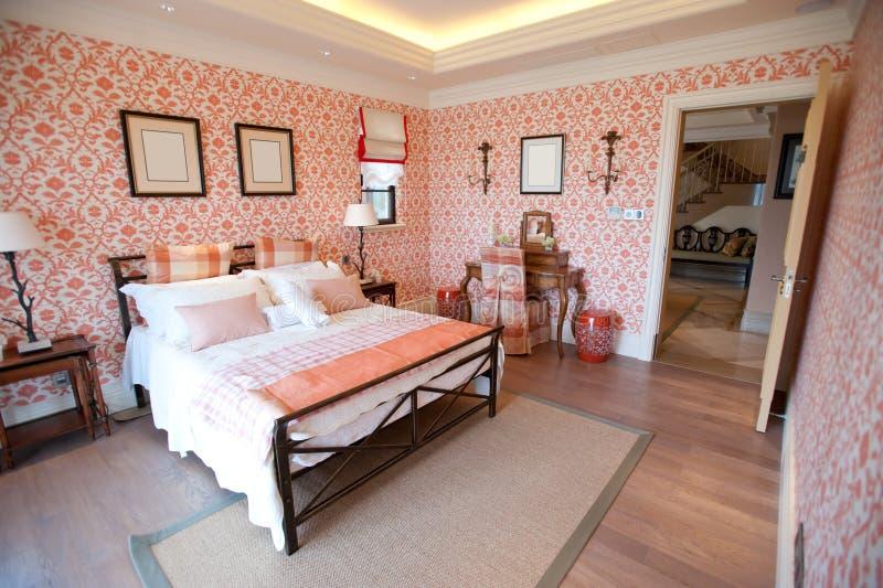 Dormitorio con el papel pintado rojo de la flor foto de archivo
