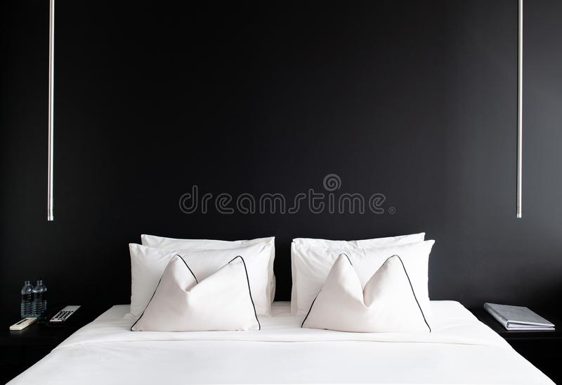 Dormitorio con la cama blanca de la pared negra, almohadas tabla lateral moderna, la fotos de archivo libres de regalías