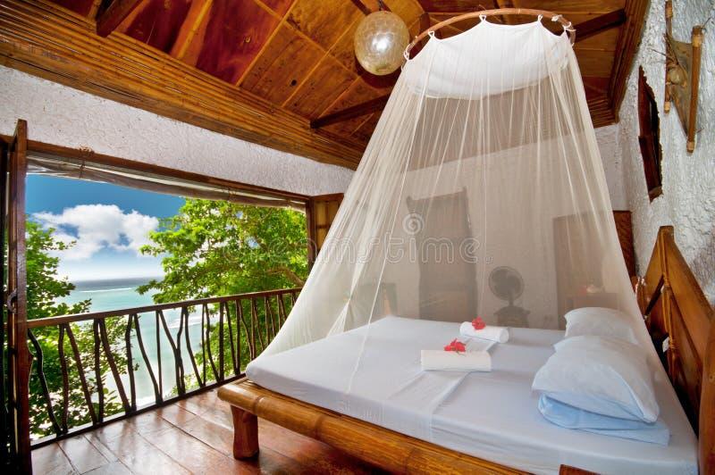Dormitorio con la cama del pabellón con la opinión del mar fotografía de archivo