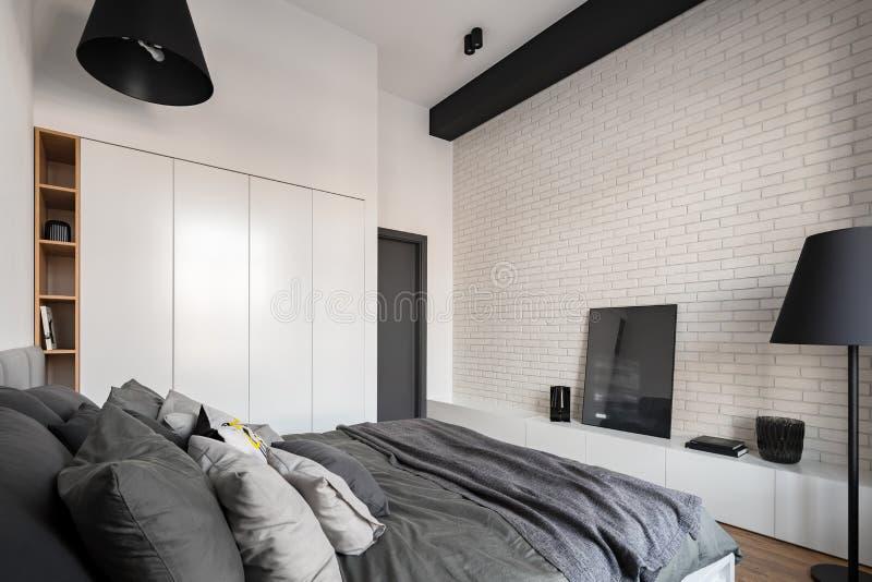 Dormitorio con la pared de ladrillo blanca imágenes de archivo libres de regalías