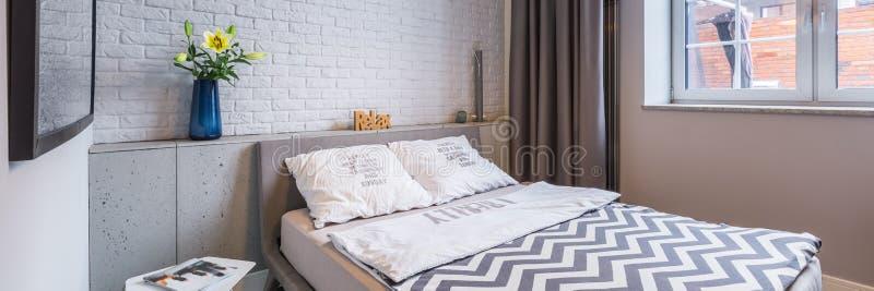 Dormitorio con la ventana y la cama fotos de archivo