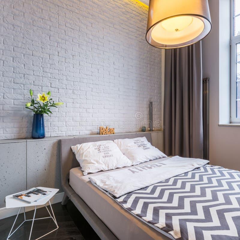 Dormitorio con la ventana y la cama imágenes de archivo libres de regalías