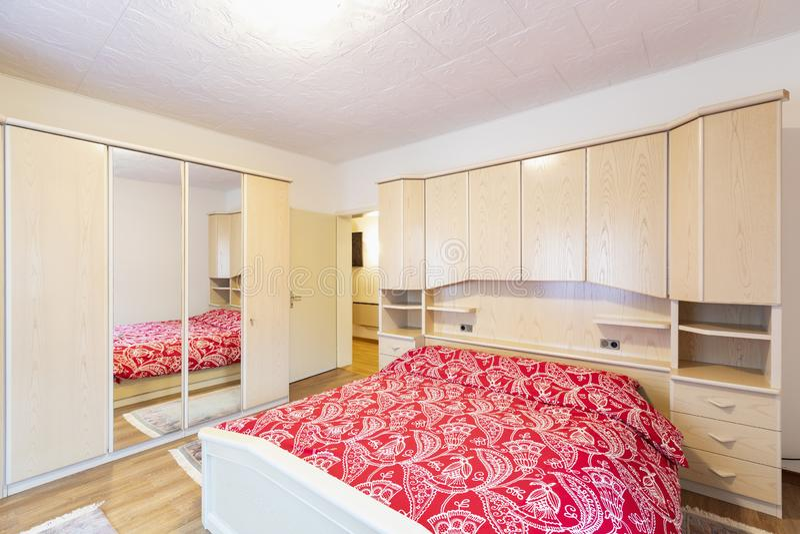 Dormitorio con las mantas rojas y el guardarropa de madera fotografía de archivo libre de regalías