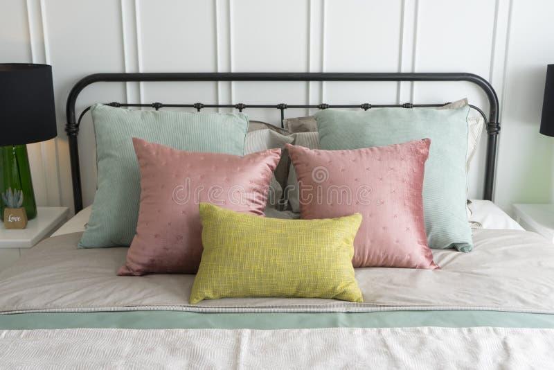 Dormitorio con rosa en colores pastel y las almohadas verdes de los acentos fotos de archivo