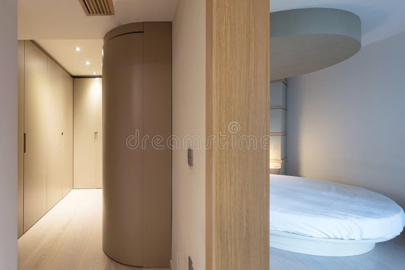 Dormitorio con una cama redonda y un vestuario colindante imagen de archivo