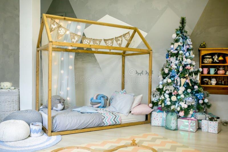 Dormitorio de los niños adornado para la Navidad Cama grande del marco de madera con las almohadas y los juguetes de la felpa, ár foto de archivo