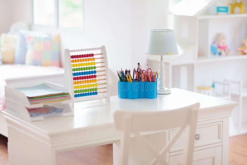 Dormitorio de los niños con el escritorio y la casa de muñecas de madera imágenes de archivo libres de regalías