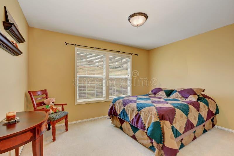 Dormitorio de los niños con la cama colorida y las paredes amarillas en colores pastel imágenes de archivo libres de regalías
