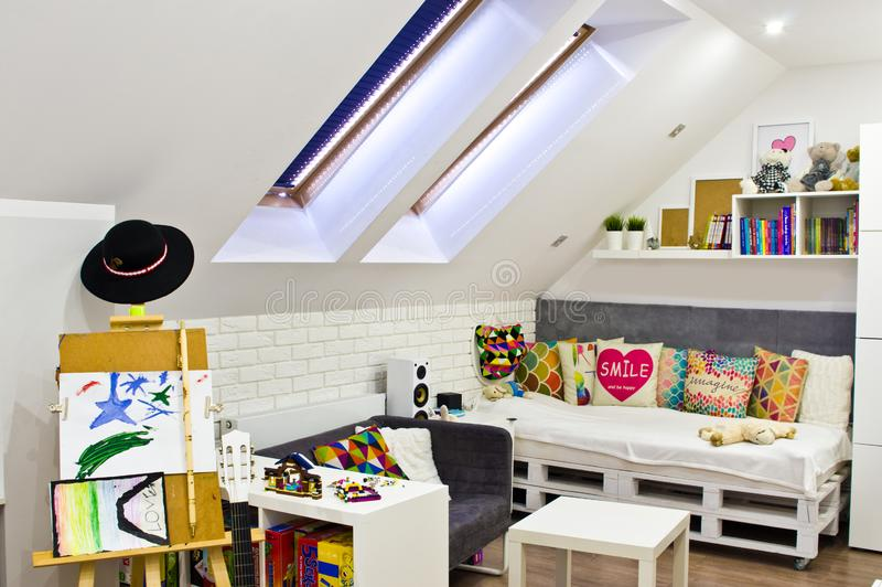Dormitorio de los niños del desván con muebles y juguetes coloridos fotografía de archivo