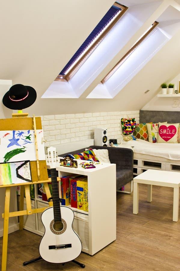 Dormitorio de los niños del desván con muebles y juguetes coloridos imagen de archivo