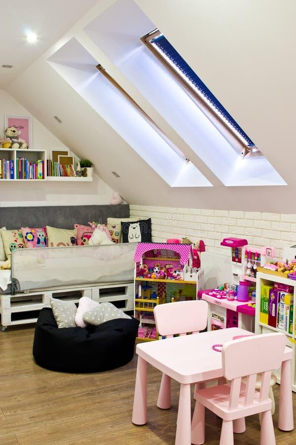 Dormitorio de los niños del desván con muebles y juguetes coloridos imágenes de archivo libres de regalías