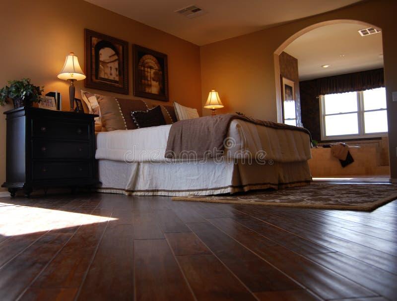 Dormitorio de lujo con el suelo de la madera dura foto de archivo libre de regalías