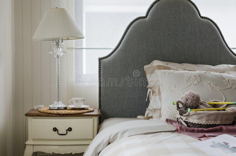 Dormitorio de lujo con la lámpara en la tabla foto de archivo