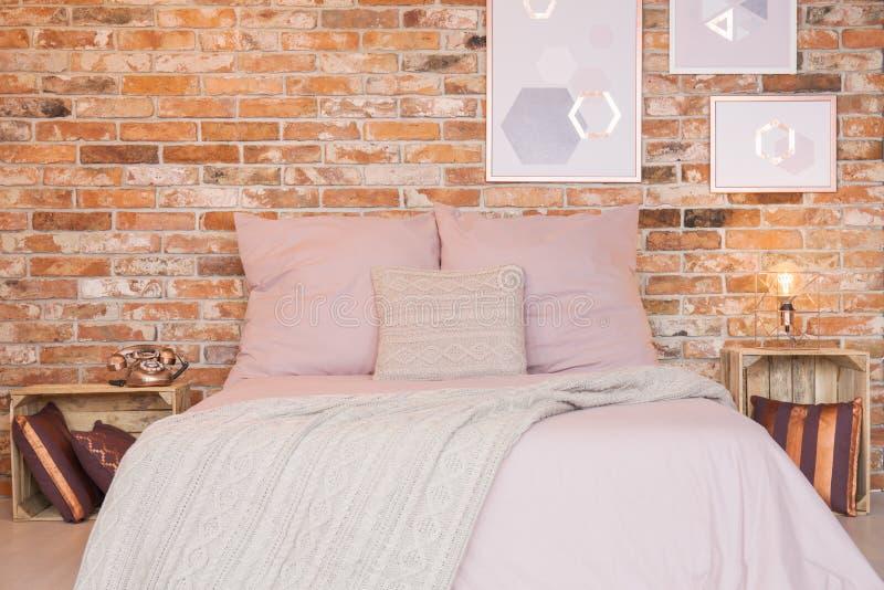 Dormitorio del desván con la pared de ladrillo imágenes de archivo libres de regalías