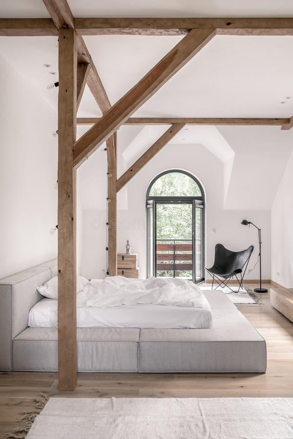 Dormitorio elegante en estilo moderno con los haces de madera fotos de archivo