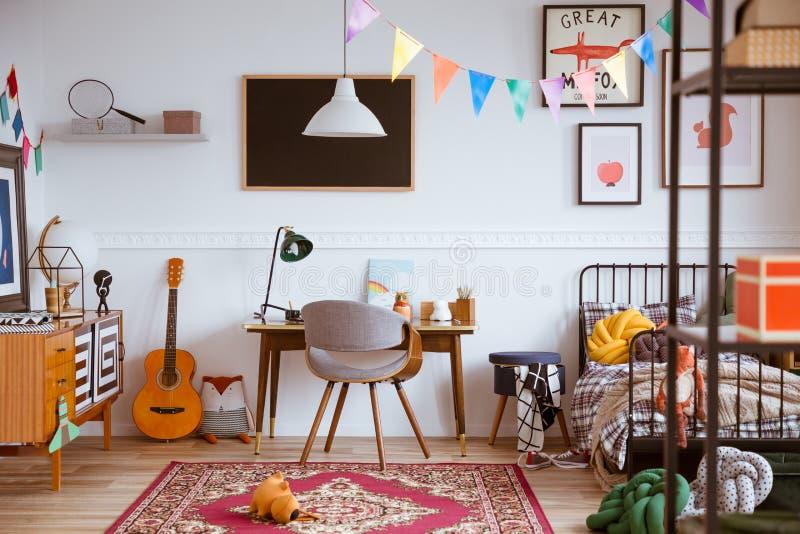 Dormitorio genderless colorido con la sola cama y muebles retros foto de archivo