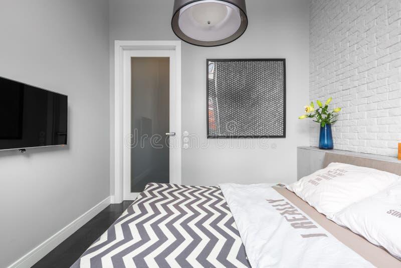 Dormitorio gris con la TV fotografía de archivo libre de regalías